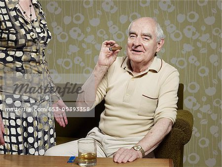 Senior man sitting on couch smoking cigar Stock Photo - Premium Royalty-Free, Image code: 653-05393358