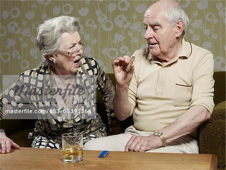 Senior woman looks shocked as senior man smokes cigar Stock Photo - Premium Royalty-Free, Image code: 653-05393366