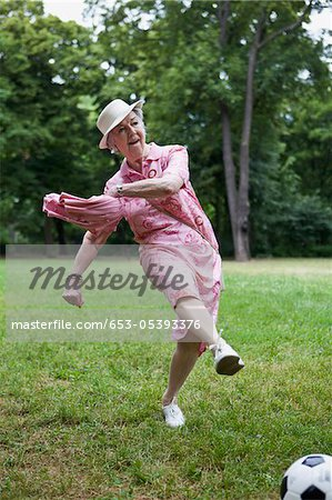 Senior woman kicks football n the park Stock Photo - Premium Royalty-Free, Image code: 653-05393376