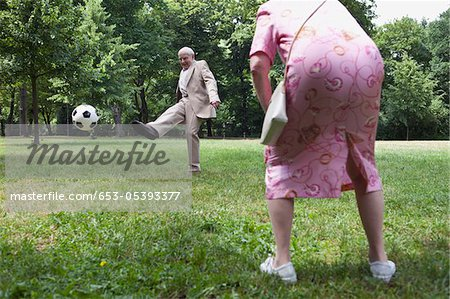 Senior couple play football in the park Stock Photo - Premium Royalty-Free, Image code: 653-05393377