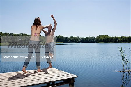 Girl on jetty pushes guy into water Stock Photo - Premium Royalty-Free, Image code: 653-05393452