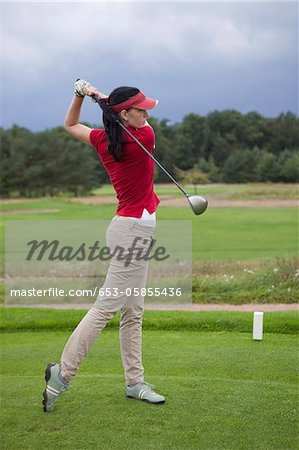 A female golfer teeing off Stock Photo - Premium Royalty-Free, Image code: 653-05855436