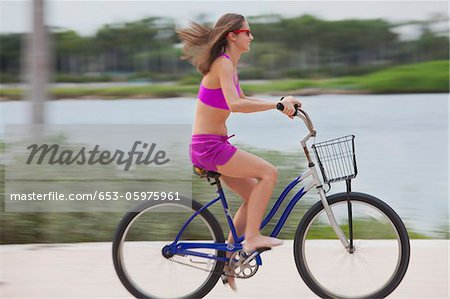 Girl cycling barefoot Stock Photo - Premium Royalty-Free, Image code: 653-05975961