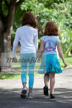 Girls walking through park hand in hand Stock Photo - Premium Royalty-Free, Image code: 653-05975989