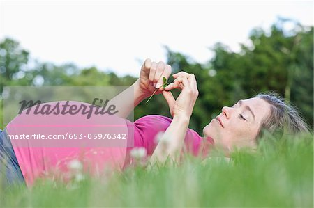 A pregnant woman lying in the grass, side view Stock Photo - Premium Royalty-Free, Image code: 653-05976342