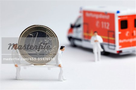 Miniature paramedic figurines carrying a euro coin on a stretcher to a toy ambulance