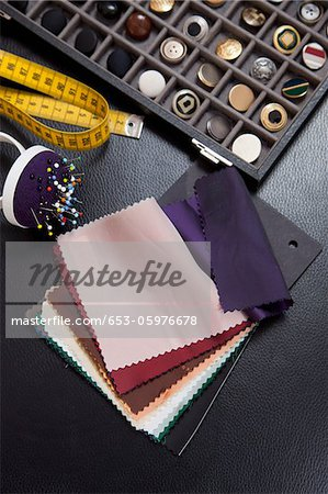 Detail of fabric samples, buttons, and other sewing equipment Stock Photo - Premium Royalty-Free, Image code: 653-05976678