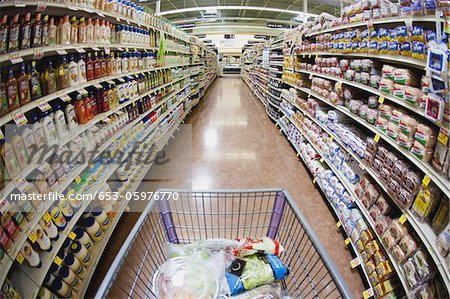 A shopping cart on an aisle in a supermarket, personal perspective Stock Photo - Premium Royalty-Free, Image code: 653-05976770