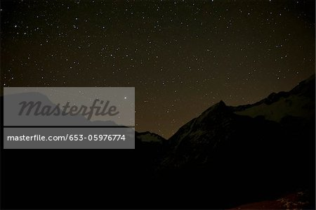 A starry sky behind silhouetted mountains