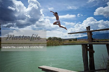 A young boy jumping into a lake Stock Photo - Premium Royalty-Free, Image code: 653-05976787