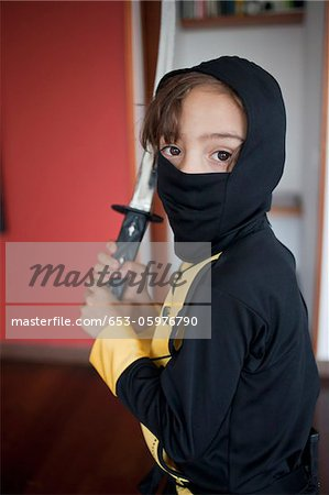 A boy dressed in a ninja costume holding a samurai sword Stock Photo - Premium Royalty-Free, Image code: 653-05976790