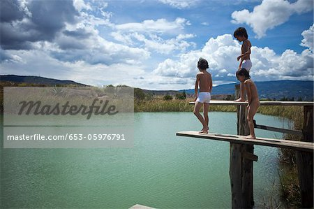 Twin brothers and their friend preparing to jump into a lake Stock Photo - Premium Royalty-Free, Image code: 653-05976791
