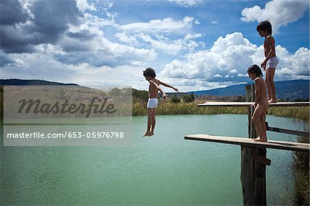 A boy jumping into water while his twin brother and friend watch Stock Photo - Premium Royalty-Free, Image code: 653-05976798