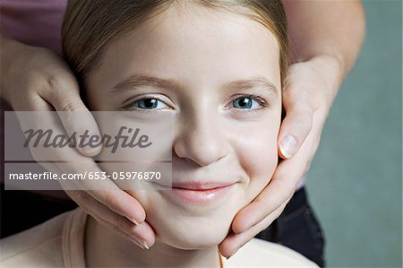 Portrait of daughter with Mother's hands on her cheeks Stock Photo - Premium Royalty-Free, Image code: 653-05976870
