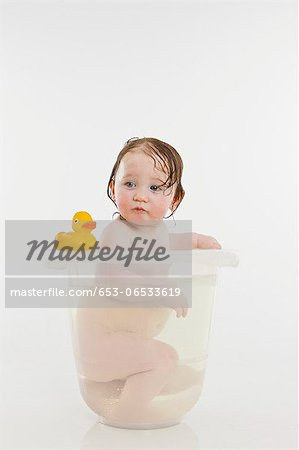 A baby girl in a bucket of water Stock Photo - Premium Royalty-Free, Image code: 653-06533619