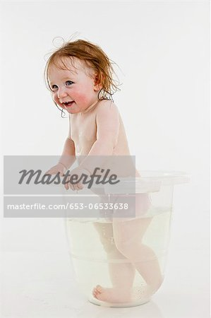 A baby girl standing in a bucket of water Stock Photo - Premium Royalty-Free, Image code: 653-06533638