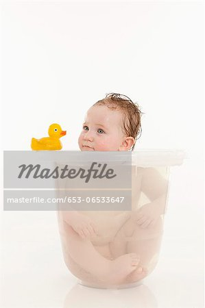 A baby girl sitting in a bucket of water Stock Photo - Premium Royalty-Free, Image code: 653-06533647
