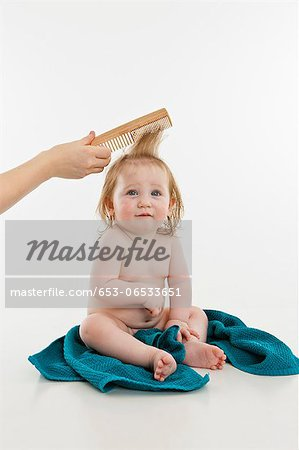 A baby girl having her hair combed Stock Photo - Premium Royalty-Free, Image code: 653-06533651