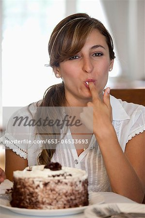 A young woman tasting a cake Stock Photo - Premium Royalty-Free, Image code: 653-06533693