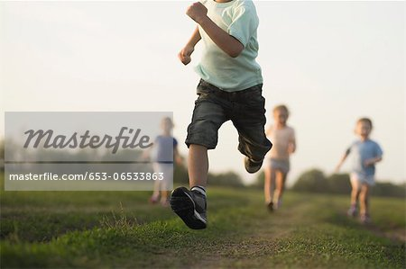 Low view of a boy running in a field with other children behind Stock Photo - Premium Royalty-Free, Image code: 653-06533863