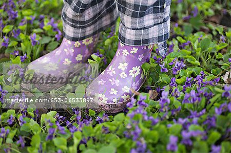 Low section of a girl standing in a garden with gumboots Stock Photo - Premium Royalty-Free, Image code: 653-06533897