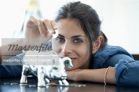 Woman putting coin into piggy bank Stock Photo - Premium Royalty-Free, Image code: 653-06534012