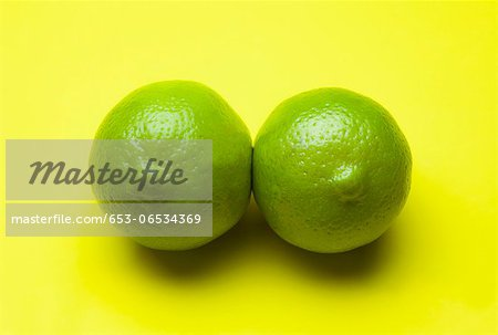Two limes arranged to look like a pair of breasts Stock Photo - Premium Royalty-Free, Image code: 653-06534369