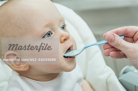 Mother spoon feeding her son on high chair Stock Photo - Premium Royalty-Free, Image code: 653-06534580