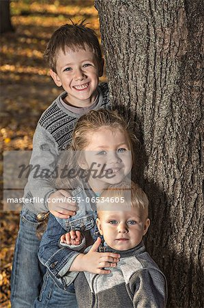 Three cheerful siblings posing next to a tree trunk Stock Photo - Premium Royalty-Free, Image code: 653-06534605
