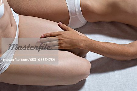 A couple in their underwear on a bed, close-up, midsection Stock Photo - Premium Royalty-Free, Image code: 653-06534759