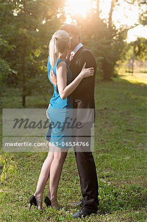 An elegantly dressed man kissing his girlfriend passionately while squeezing her bottom Stock Photo - Premium Royalty-Free, Image code: 653-06534766