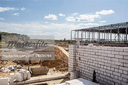 A cement mixer and brick wall in front of a construction frame at a construction site Stock Photo - Premium Royalty-Free, Image code: 653-06534784