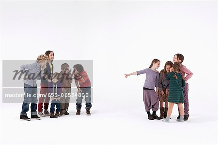 A group of boys laughing while a group of girls gossips about them Stock Photo - Premium Royalty-Free, Image code: 653-06534800