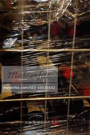 A metal crate filled with stacked red wine bottles and wrapped in plastic wrap Stock Photo - Premium Royalty-Free, Image code: 653-06535052