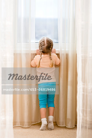 Little girl on her tiptoes trying to see out window Stock Photo - Premium Royalty-Free, Image code: 653-06819486