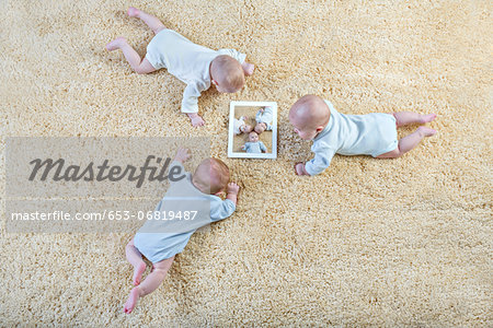 Three babies look at a picture of themselves on a digital tablet Stock Photo - Premium Royalty-Free, Image code: 653-06819487
