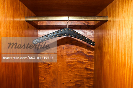 Studded leather belt hanger in wardrobe Stock Photo - Premium Royalty-Free, Image code: 653-06819626