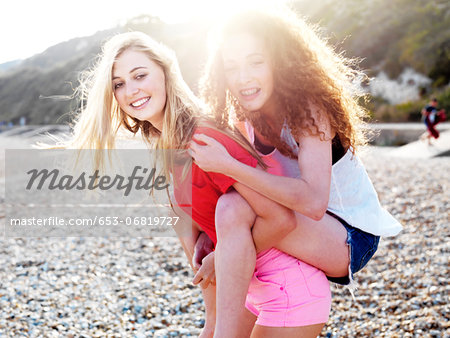 A young woman giving her teenage friend a piggyback ride at the beach Stock Photo - Premium Royalty-Free, Image code: 653-06819727