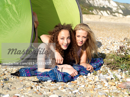 Two friends lying partially inside a beach tent on a rocky beach Stock Photo - Premium Royalty-Free, Image code: 653-06819731
