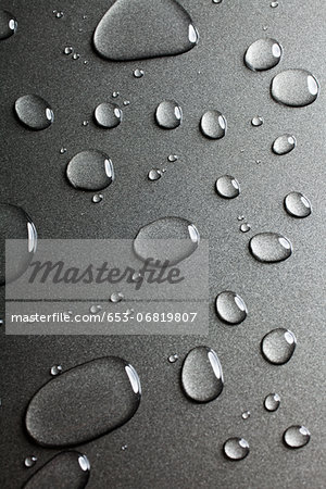 A pattern of various shaped water drops on a nonstick baking sheet Stock Photo - Premium Royalty-Free, Image code: 653-06819807
