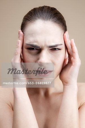 A grimacing young woman with her hands to her temples Stock Photo - Premium Royalty-Free, Image code: 653-06819827