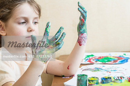Girl looking at her painted hands Stock Photo - Premium Royalty-Free, Image code: 653-07233760