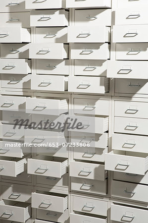 A white cabinet with drawers opened at varying degrees Stock Photo - Premium Royalty-Free, Image code: 653-07233806