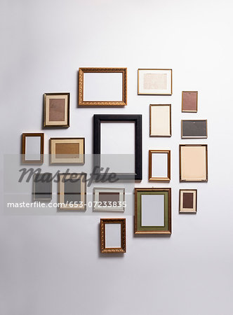 Various empty picture frames hanging on a wall Stock Photo - Premium Royalty-Free, Image code: 653-07233835