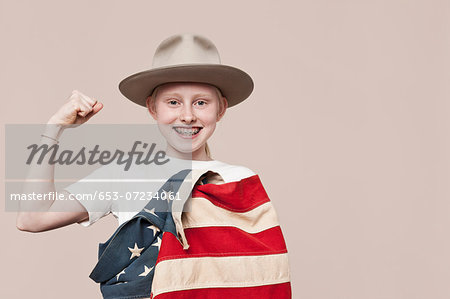 A smiling girl wearing a ranger hat wrapped in an American flag and making a fist Stock Photo - Premium Royalty-Free, Image code: 653-07234061