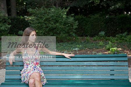 Young woman sitting on park bench Stock Photo - Premium Royalty-Free, Image code: 653-07539011