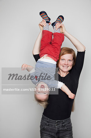 Mother holding baby boy upside down Stock Photo - Premium Royalty-Free, Image code: 653-07539033