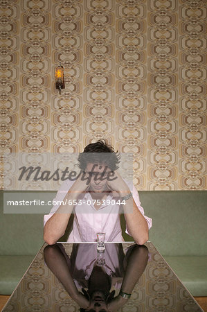 A depressed man looking down at a shot glass Stock Photo - Premium Royalty-Free, Image code: 653-07539044