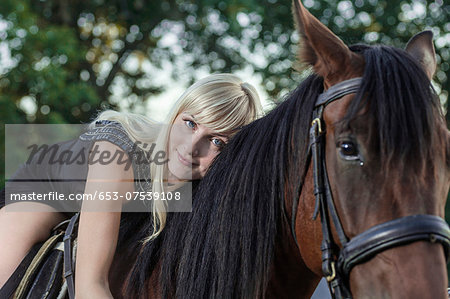 Young woman lying on horse Stock Photo - Premium Royalty-Free, Image code: 653-07539108