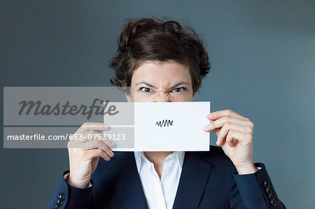 Portrait of mid adult woman holding paper with zigzag sign, close-up Stock Photo - Premium Royalty-Free, Image code: 653-07539123
